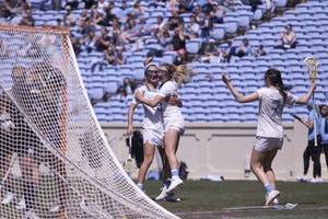 Sophomore attacker Katie Hoeg (8) and first-year attacker Jamie Ortega (3) celebrate Ortega's goal against Notre Dame on March 31 in Kenan Stadium.