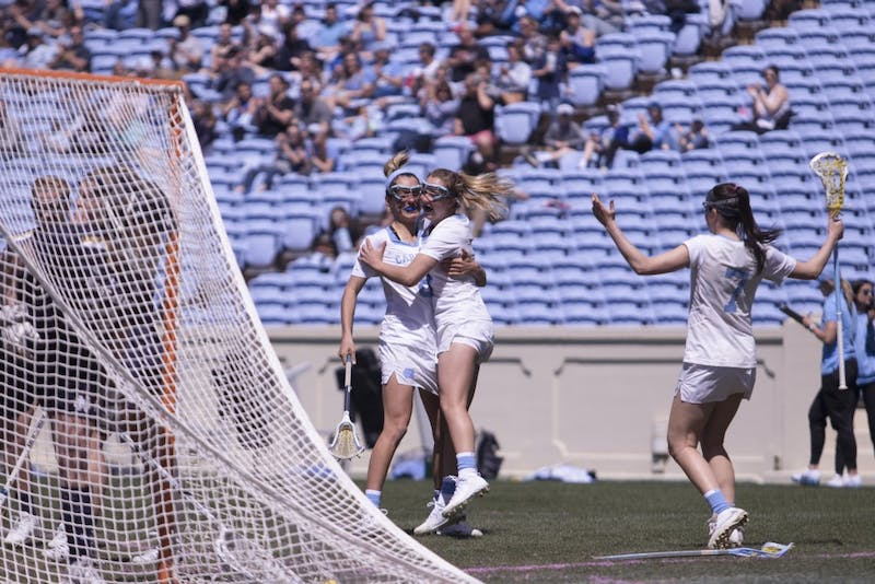 Sophomore attacker Katie Hoeg (8) and first-year attacker Jamie Ortega (3)celebrate Ortega's goal against Notre Dame on March 31 in Kenan Stadium.
