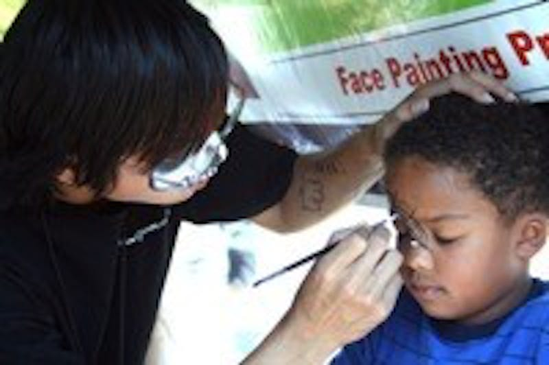 Kelly Kuo of Paint Savvy paints webs and a spider on six year-old Austin Thompkins face during Chapel Hill's 36th annual Festifall on Sunday.