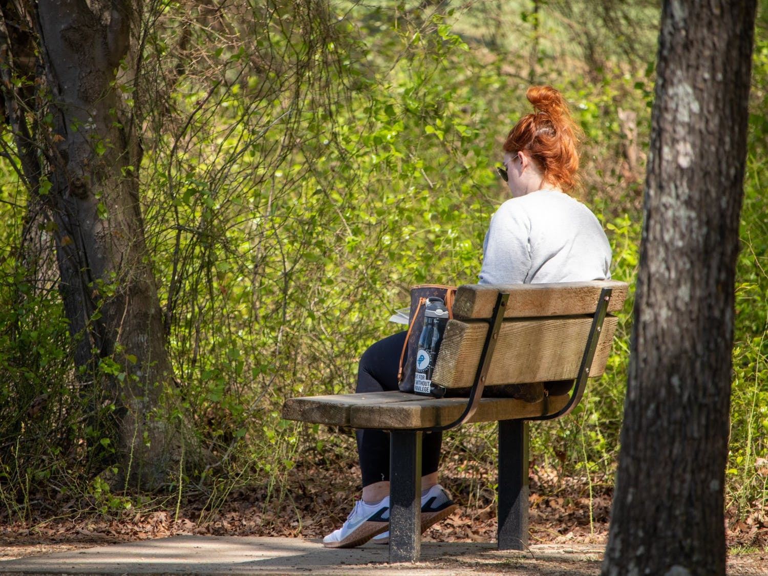 A woman reads a book in Jetton Park in Cornelius, NC on Monday, April 12, 2021.