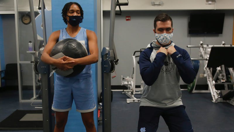 Women's basketball strength coach Caleb Krueger assists first-year guard Kennedy Todd-Williams during a preseason workout October 1, 2020 in Carmichael Arena. Photo courtesy of UNC Athletics Communications.