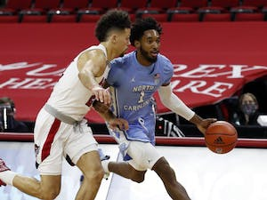 North Carolina's Leaky Black (1) drives past N.C. State's Devon Daniels (24) during the first half of N.C. State's game against UNC at PNC Arena in Raleigh, N.C., Tuesday, December 22, 2020. Photo courtesy of Ethan Hyman.