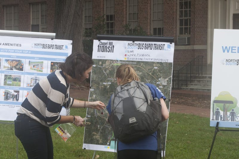 Katherine Shor, a Renaissance Planning team member, shows a Three Zeros Day attendee what steps Chapel Hill Transit has taken to prepare for the Three Zeros Environmental Initiative in Polk Place on Tuesday, Sept. 25.