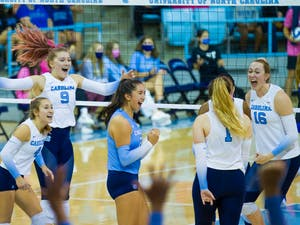 UNC women's volleyball players celebrate after scoring a point at the game against Duke on Oct. 22 at Carmichael Arena. UNC beat Duke 3-0.