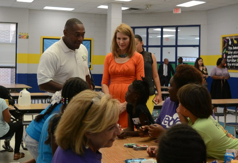 First Lady Kristin Cooper (right) and ECDI President David Reese (left) speak to students during lunchtime of the summer program at Eastway Elementary.