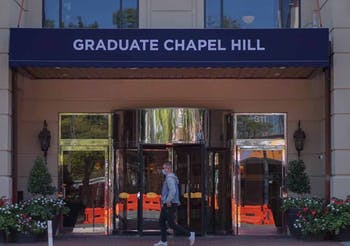 A pedestrian walks by the Graduate Hotel on Sept. 23, 2020. Hotels in Chapel Hill are dealing with the loss of business due to the lack of sports games that brings in viewers from out of town.
