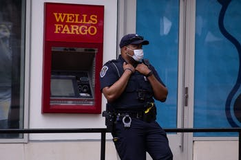 A UNC Chapel Hill police officer stands outside the Student Stores building on Thursday, Aug. 6, 2020.