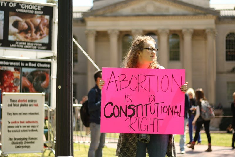 Senior geology major Michelle Gavel participates in the counter-protest against anti-abortion group the Genocide Awareness Project. Gavel was invited to protest the display by friends with shared views, and expresses disappointment in GAP's return to campus.