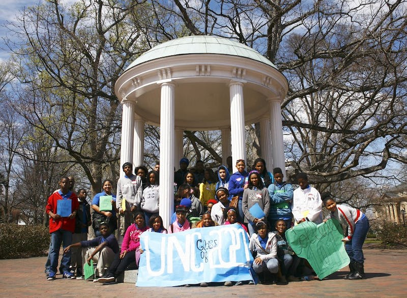 Students from Carter Community School, a charter school in Durham, participate in UNC's Students for Education Reform College 101 day. The eighth-grade students toured campus, visited science laboratories and Carmichael Arena and learned about the benefits of attending college. The students pose for a picture at the Old Well at the end of the day. They held a sign saying UNC Class of 2021.