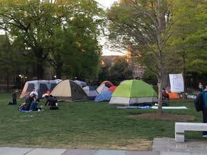 Protestors encamped on Abele Quad eat dinner before the sun sets over Duke University on Monday evening. Volunteer faculty and organizations such as the Duke Center for Multicultural Affairs donated seventeen tents, food and other supplies to the protesters.