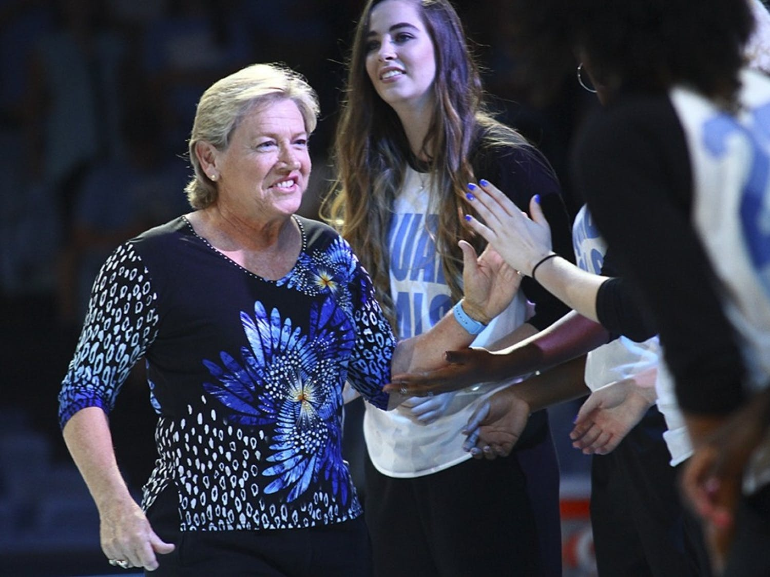 Sylvia Hatchell high-fives her players at the 2016 Late Night With Roy event in the Smith Center.