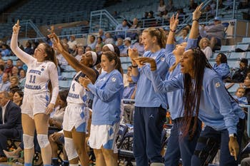 The UNC women's basketball team cheers from the sideline. The Tar Heels beat the Buccaneers 85-54 on Friday, Nov, 15, 2019 at Carmichael Arena.