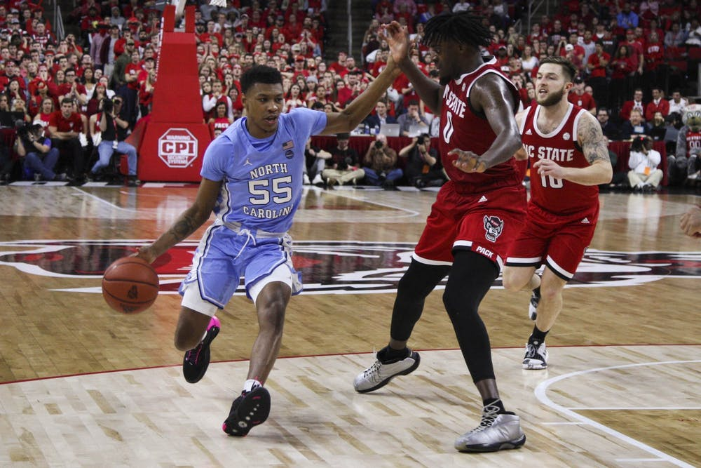 <p>Graduate guard Christian Keeling (55) runs the ball down the court during the game against N.C. State in the PNC Arena on Monday, Jan. 27, 2020. UNC defeated N.C. State for the seventh time consecutively at the PNC Arena 75-65.</p>