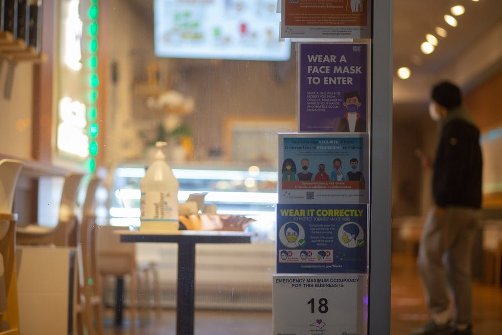 <p>Signs urging patrons to wear a mask outside of Möge Tee on Franklin Street on Feb. 2, 2021.</p>