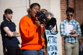 "De'Ivyion Drew, a sophomore and member of the Campus Safety Commission, speaks into a megaphone to address a crowd during a press conference hosted by campus activists at the Peace and Justice Plaza on Nov. 6, 2019. ""If anything, it leads us in a circle — this circle of police violence, police oppression and the system that is UNC that silences us every single day,"" Drew says, referencing a report investigating police conduct at the University."