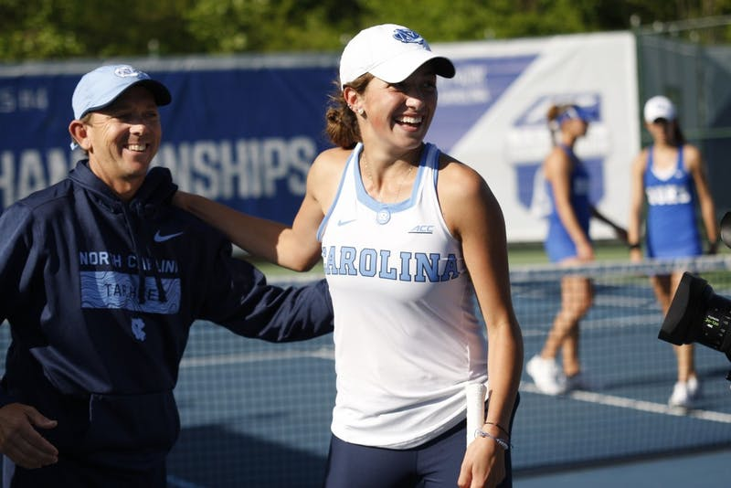 UNC women's tennis first-year Cameron Morra and head coach Brian Kalbas smile after winning the ACC Tennis Tournament in Cary, NC on Sunday April 21, 2019. UNC beat Duke 4-2.