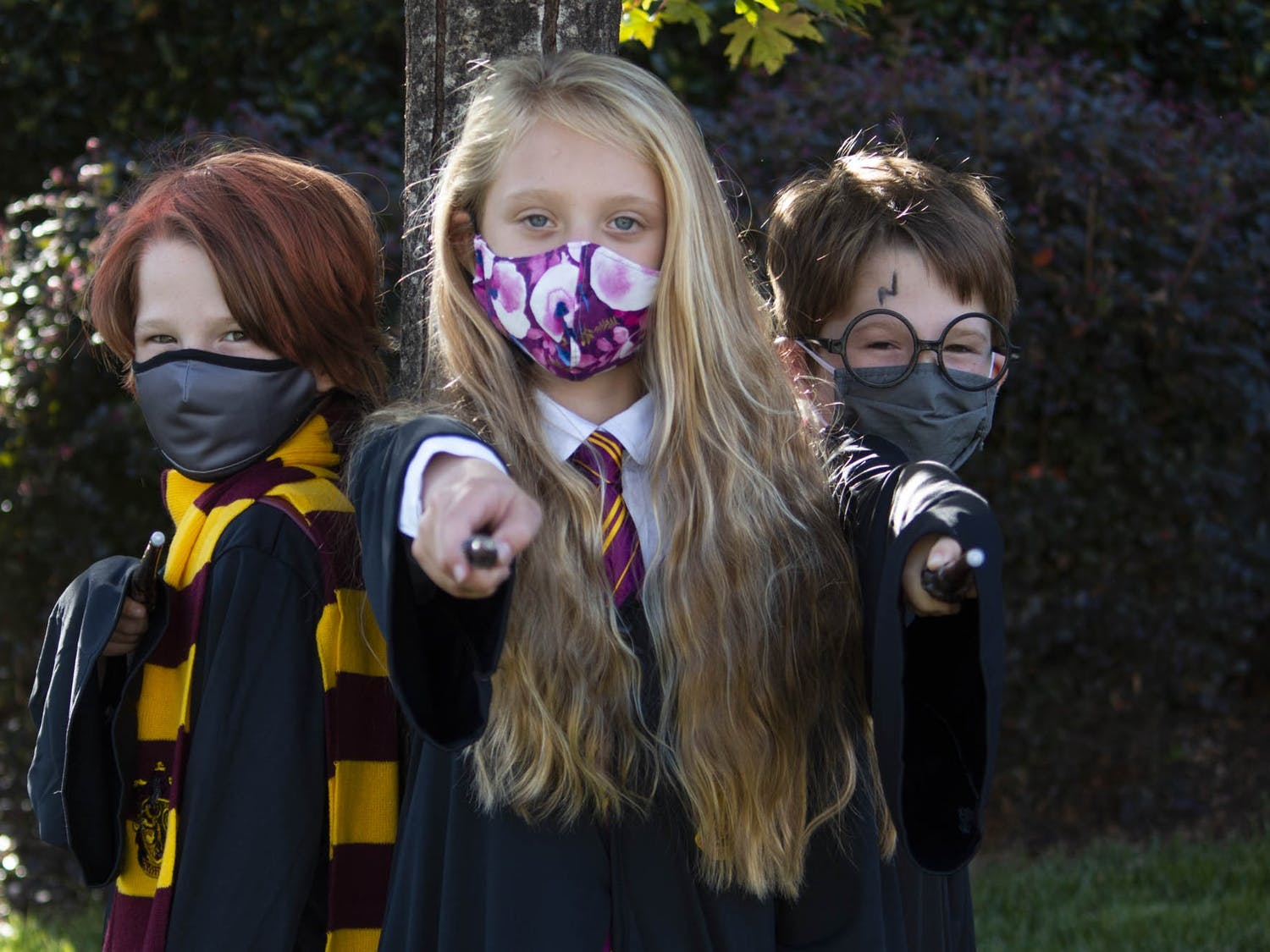 From left to right: Evan, nine, Amelia, eight and a half, and Will, nine, point their wands in preparation for Halloween night in Durham on Thursday, Oct. 22, 2020. The three, who have all known each other their whole lives, will be going as Harry, Hermione and Ron from Harry Potter. Amelia lives across the street from Evan and Will, who are identical twins and just five and a half months older than Amelia. They all agreed that they are most excited to get candy and play corn hole on Halloween.