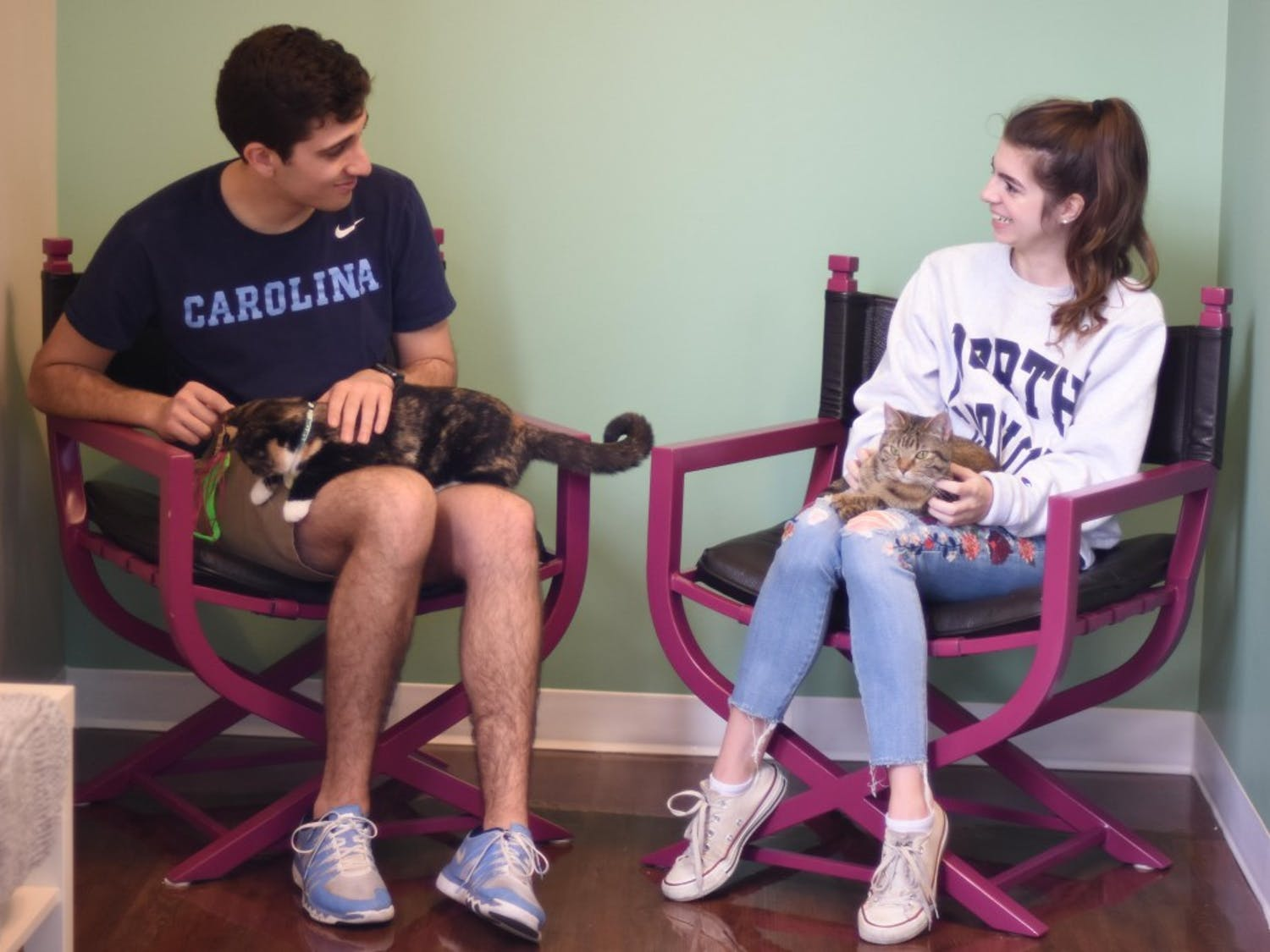 Adam Jordan and Ashley Mills, both juniors in the School of Media and Journalism, petting two of the twelve cats at Cat Tales Cat Cafe on Friday, Feb. 15, 2019. The cafe creates a low stress place for adoptable cats and cat lovers to meet and socialize.