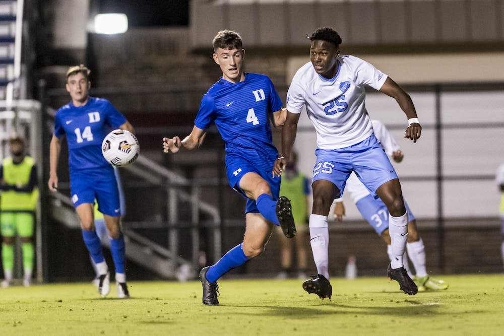 <p>&nbsp;UNC freshman forward Akeim Clark (25) races Duke players for the ball at the game on Friday, October 2, 2020 in Koskinen Stadium. UNC won 2-0.</p>