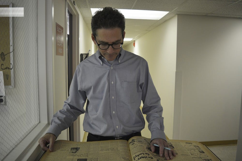 UNC Archivist Nicholas Graham works on preserving UNC history through the many documents and artifacts that come through his office in Wilson Library. Here he looks over an archived copy of The Daily Tar Heel from 1951 for an upcoming exhibit.
