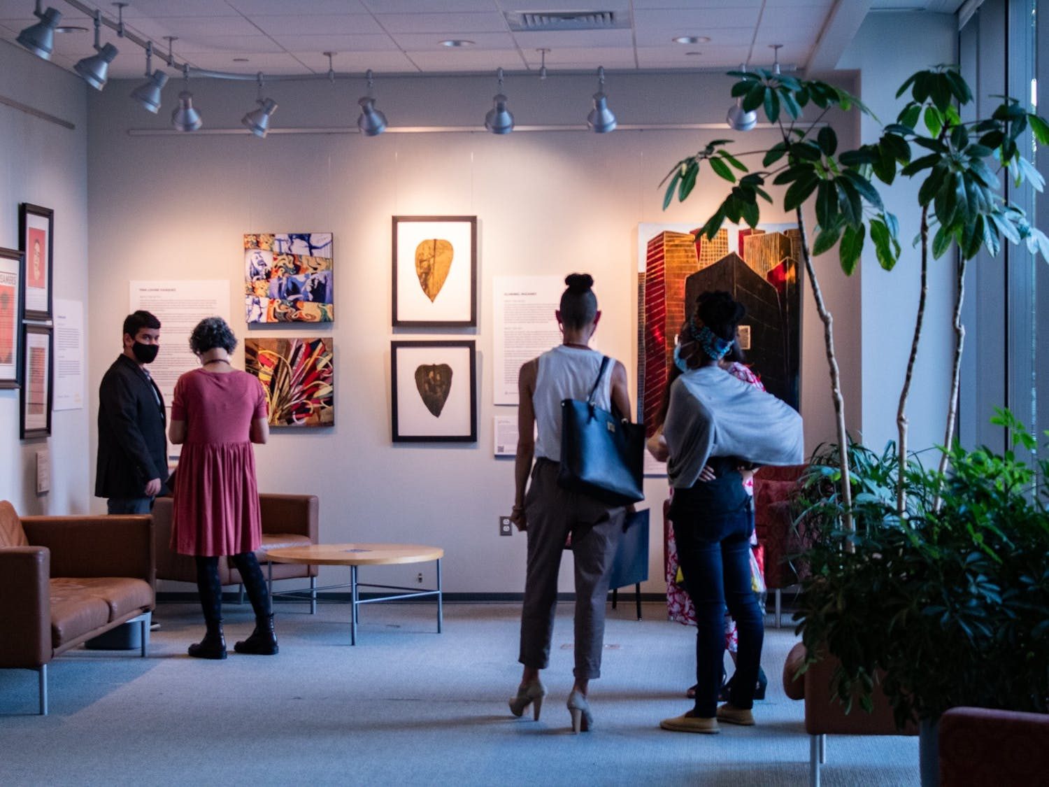 Artists and viewers admire the art of the thirteen LatinX artists on display for the Being and Belonging exhibit at the Fedex Global Center on Oct. 5.