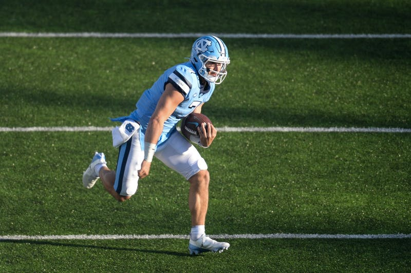 UNC's sophomore quarterback Sam Howell runs the ball downfield during a game in Kenan Memorial Stadium during a game against Wake Forest on Saturday, Nov. 14, 2020. UNC beat Wake Forest 59-53.
