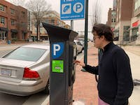 Community member Stefan Hartelt interacts with the parking meter outside of Target on Franklin Street.