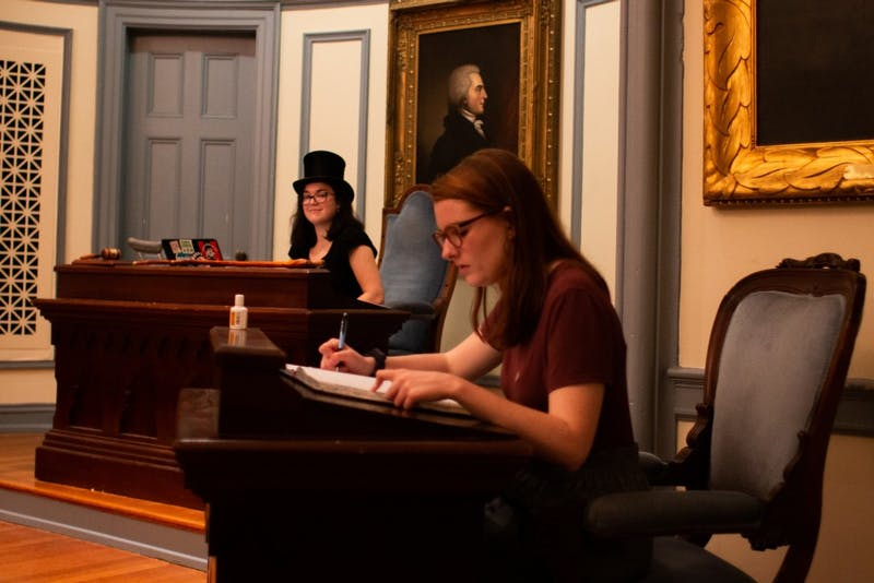 Joint Senate President and member of the Dialectic Society Katrina Smith, a senior English major, watches as Sergeant-at-Arms Maggie Pollard, a sophomore political science and public policy double major, takes attendance of Di Phi senators at the society's weekly Monday meeting in New West on Monday, April 8, 2019. Smith wears a top hat and carries a cane as she officiates the meetings and debates. As president of the joint senate, she also wields the power to break ties as in Monday's debate over whether the society would support a motion to ban homeschooling in the country. After an 11-11 tie between both societies, the motion failed with Smith's tiebreaker.