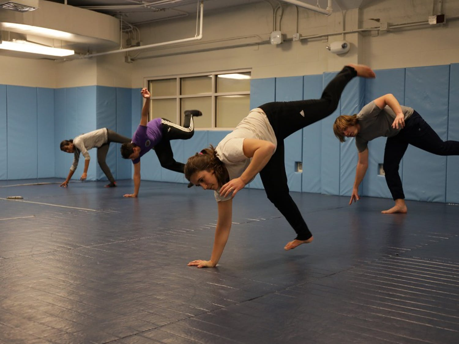 Quinn Hoffman (center) leads (from left to right) Maudrie Alexis, Joe Garay and Andrew Tillett in capoeira exercises Thursday night.