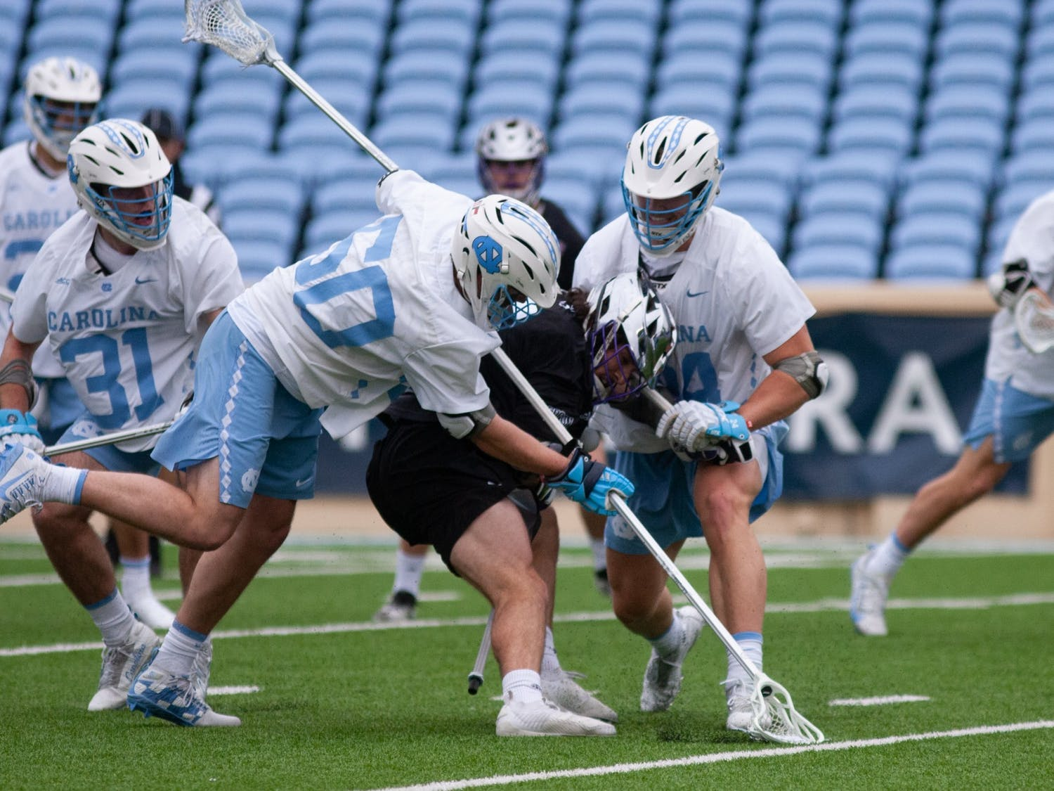 Sophomore defenseman Collin Loughead (50) and junior defenseman Will Bowen (24) try to take possession of the ball. UNC wins against High Point 27-12 at Kenan Stadium on Saturday, Feb. 27, 2021.