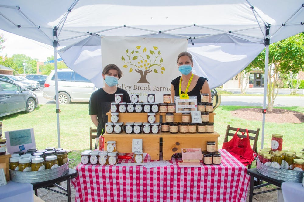 Andrea Davis, owner of Valley Brook Farms, stands with co-worker Matthew Pittman behind their booth at the Carrboro Farmers Market on Wednesday June 9, 2021. Valley Brook Farms is a local farm that makes a variety of jams, jellies, and pickled goods.