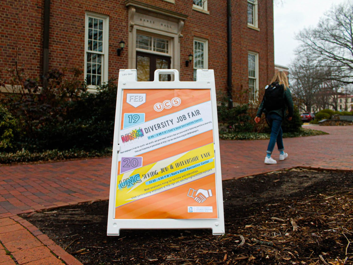A UNC student walks past an advertisement outside Hanes Hall for the Diversity Job Fair on Wednesday, Feb. 19, 2020. The fair hosts students and employers who are interested in careers that promote diversity. The fair will take place on Wednesday, Feb. 19 from 12 to 4 p.m. at Ram's Head Recreation Center.