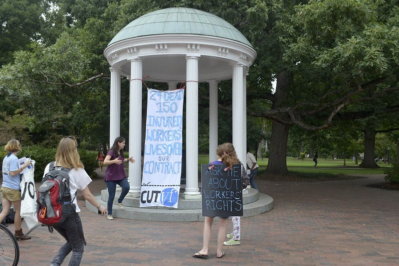 Members of SAW with their banner at the Old Well on Wednesday afternoon.  The banner was hung in hopes to gain the attention of Chancellor Folt and UNC students.