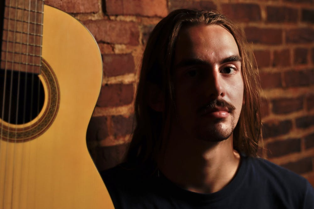 """DTH Photo Illustration. Assistant Photo Editor Ira Wilder poses by a guitar as he prepares to review Kacey Musgrave's new genre-bending country album, """"star-crossed."""""""
