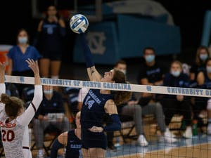 Sophomore middle and outside hitter Kaya Merkler (14) jumps to spike the ball in the UNC Women's volleyball game against Virginia Tech at the Woolen Gymnasium on Oct. 10. The Heels won 3-0.
