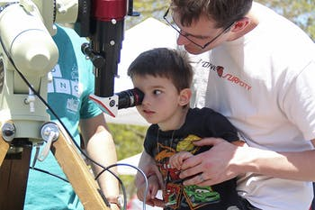 Max Brueseke looks through a telescope with the help of his father at the NC Science Expo on Saturday.