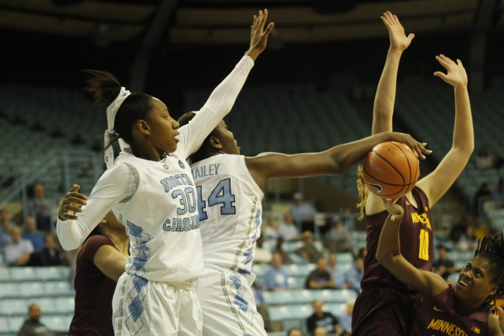 <p>Forward Jaelynn Murray (30) and center Janelle Bailey (44) block the ball during a Nov. 29 game against Minnesota at Carmichael Arena.</p>