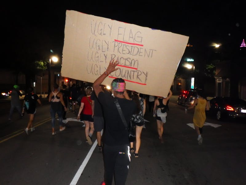 A protestor holds a large sign behind a crowd at the Raleigh Black Lives Matter protest on Friday, Aug. 28, 2020.