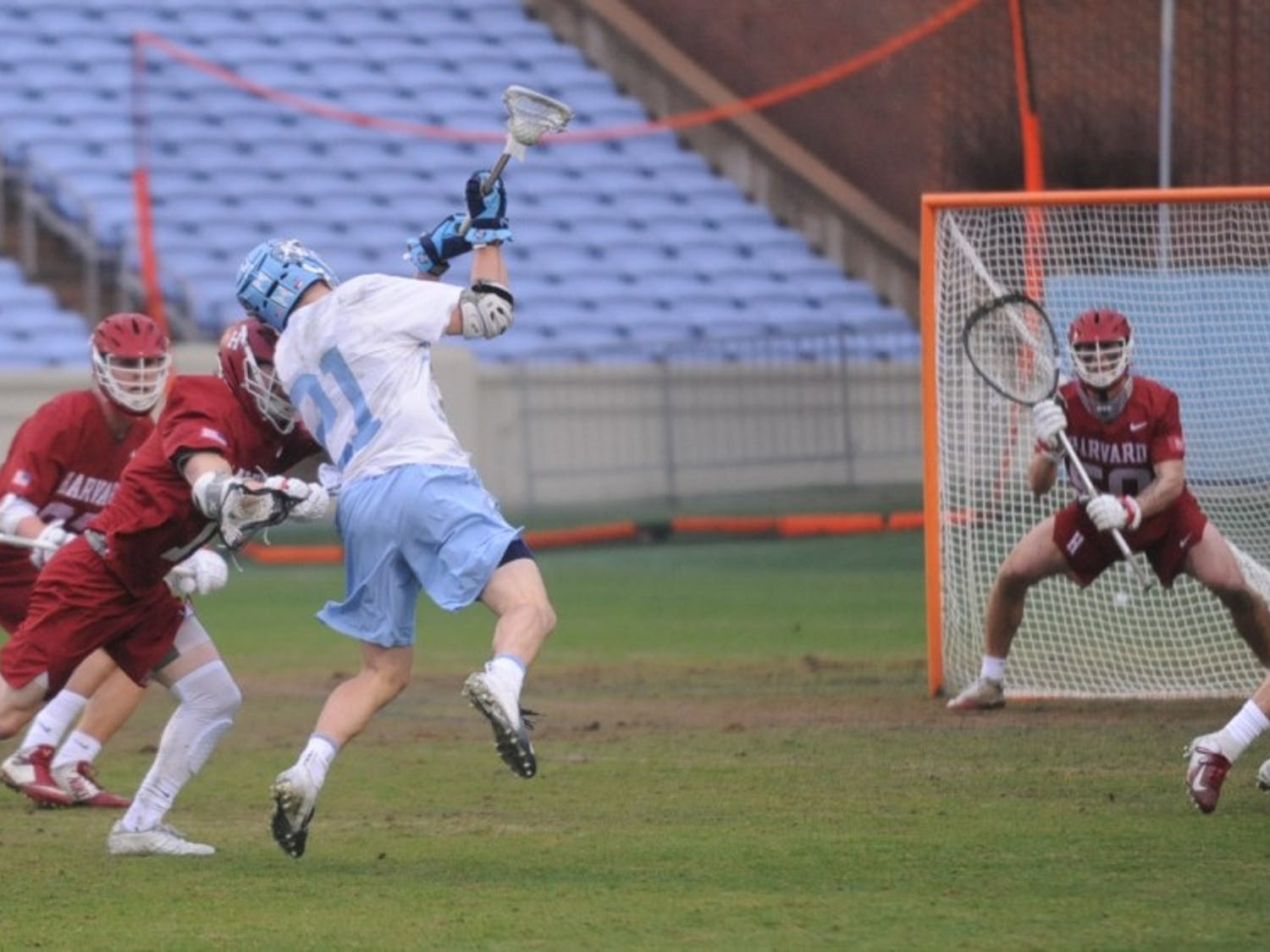 Midfielder Justin Anderson (21) shoots during the game against Harvard in Kenan Stadium on Saturday, Feb. 16, 2019. UNC won 16-11.