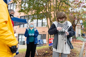 """UNC sophomore Samantha Beecham puts on an """"I Voted"""" sticker after voting at the Carrboro Town Hall on Sunday, Oct. 25, 2020."""