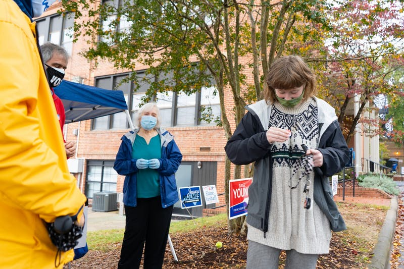 "UNC sophomore Samantha Beecham puts on an ""I Voted"" sticker after voting at the Carrboro Town Hall on Sunday, Oct. 25, 2020."