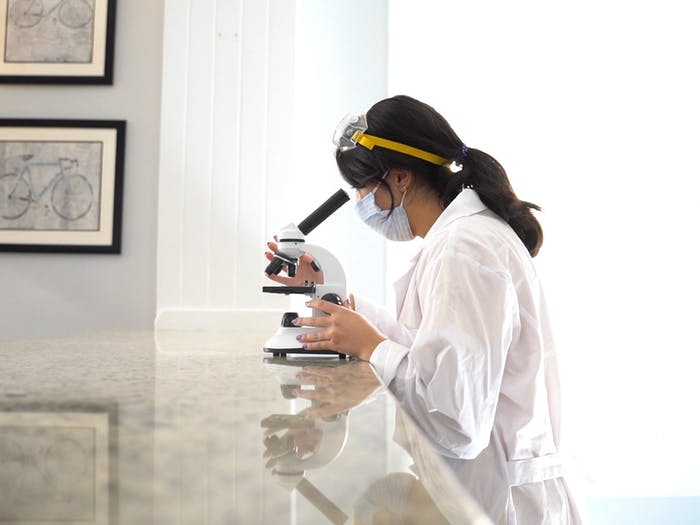 DTH Photo Illustration depicting a student with a mask on using a microscope.