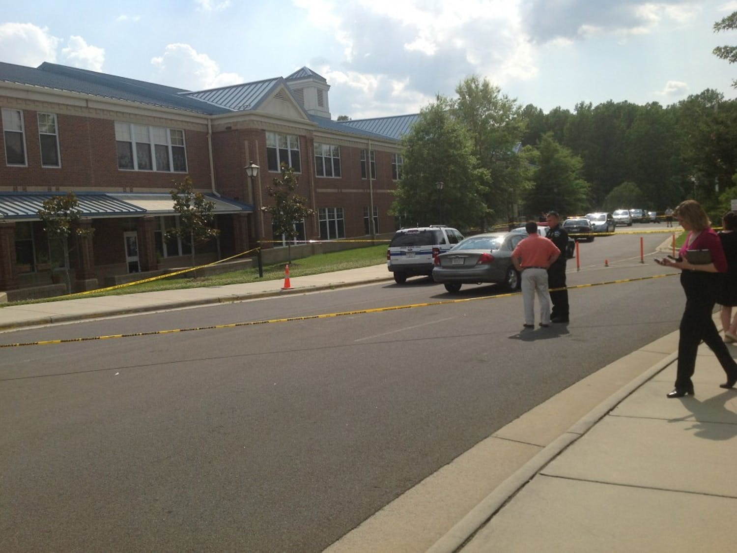 Police talk with a parent at Mary Scroggs Elementary School after a shooting on the afternoon of May 25.