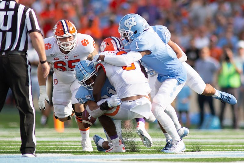 Senior safety Myles Dorn (1) and junior linebacker Chazz Surratt (21) tackle Clemson's Travis Etienne (9) on Saturday, Sept. 28, 2019 in Kenan Memorial Stadium. UNC lost its bid to upset Clemson's 19-game-winning streak 21-20.