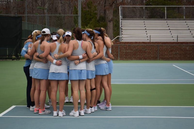 The North Carolina women's tennis team huddles before its match against N.C. State on Feb. 21 at the Cone-Kenfield Tennis Center.