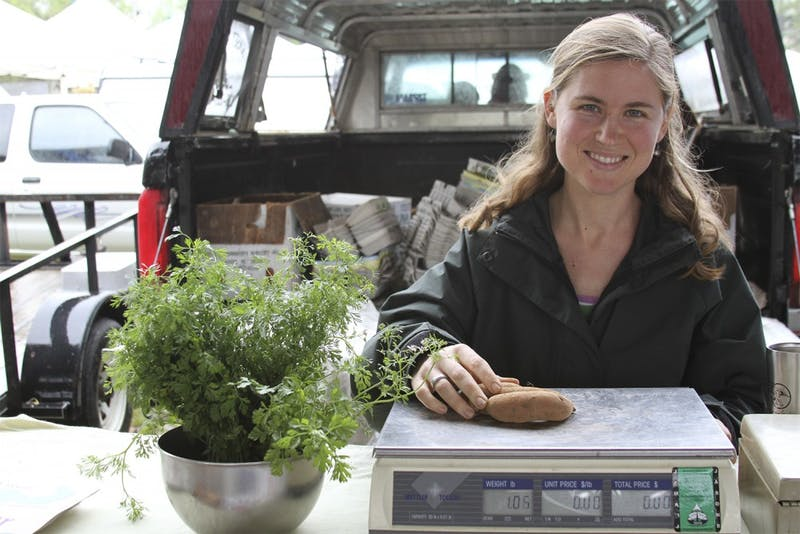 Jamie Murray, owner of Sunset Farms, weighs potatoes at the Carrboro Farmers' Market. Donations help to fund the market.