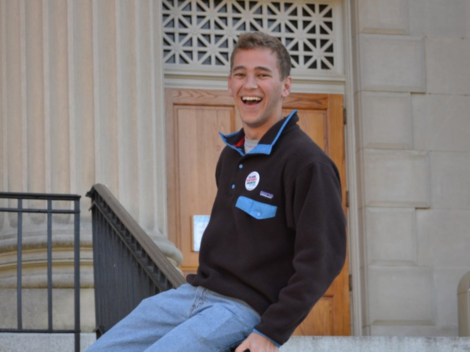 Will Leimenstoll slides down the banister in front of Wilson Library.