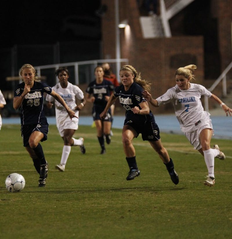 Notre Dame's Jessica Schuveiller (12) chases the ball while defending UNC's Kealia Ohai. Schuveiller scored one goal for the Fighting Irish.