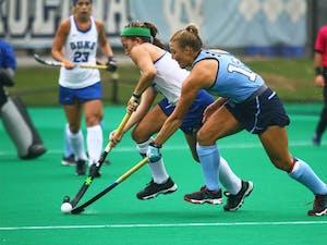 Ashley Hoffman (13) poke checks the ball from a Duke player.