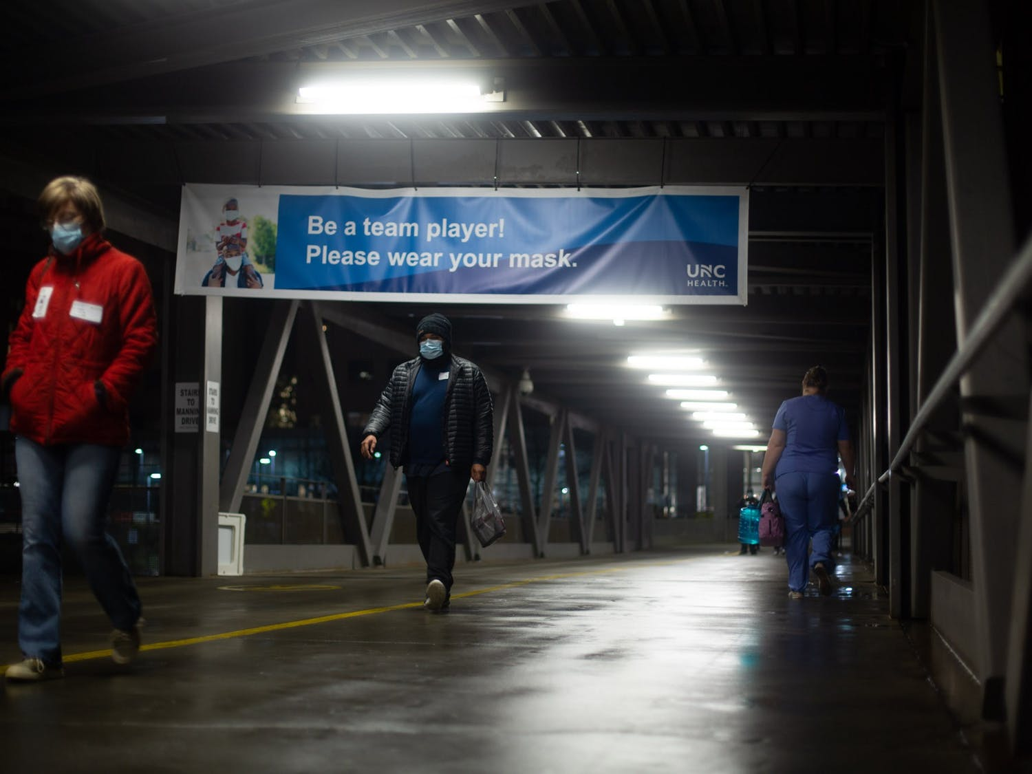 Nurses and staff at UNC Hospitals walk along the bridge over Manning Drive during a shift change on Sunday, Jan. 31 2021.